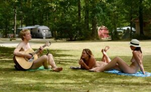 young nude people relaxing on the grass in a park