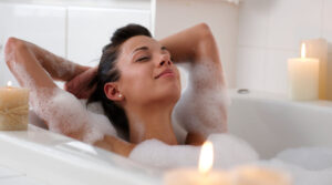 woman taking bubble bath with candles